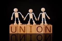 """Концепция сыгранности, ручка Figuers стоя на деревянном блоке куба с  """"UNION†слова стоковая фотография rf"""