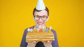 Концепция с днем рождений Молодой смешной человек с тортом o оранжевая предпосылка сток-видео