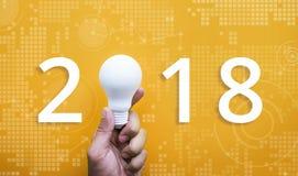 Концепция творческих способностей 2018 идей при человеческая рука держа электрическую лампочку Стоковые Фотографии RF