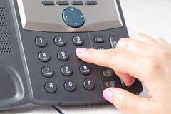 Концепция телефона центра телефонного обслуживания или офиса, женский номер прессы пальца на phonepad стоковые изображения