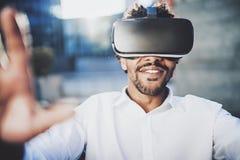 Концепция технологии, игры, развлечений и молодые люди Усмехаясь американский африканский человек наслаждаясь виртуальной реально стоковая фотография