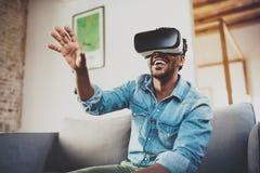 Концепция технологии, игры, развлечений и людей Счастливый бородатый африканский человек наслаждаясь стеклами виртуальной реально стоковое изображение