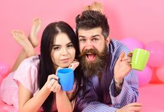 Концепция традиции семьи Человек и женщина на усмехаясь положении сторон, розовой предпосылке Пары ослабляют в утре с кофе Стоковая Фотография