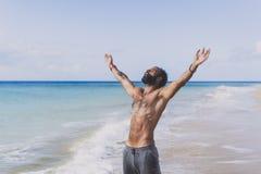Концепция тренировки разминки Здоровый красивый активный человек при тело пригонки мышечное отдыхая на пляже на утре sporty Стоковое фото RF