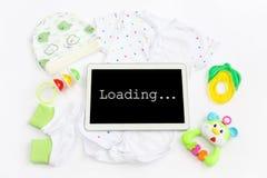 Концепция удлиняя семьи и предпологать для младенца: экранируйте таблетку с загрузкой надписи, одежду для newborn - сделанные по  Стоковая Фотография RF