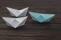 Концепция уникальности, бумажная шлюпка выдающая от других Комплект шлюпок origami на деревянном столе Стоковые Фотографии RF