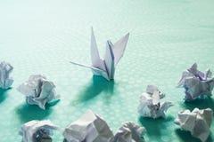Концепция успеха, origami a птица бумаги и скомканные бумажные шарики Стоковые Фото