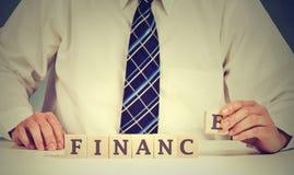 Концепция финансового рынка Бизнесмен вручает аранжировать деревянные блоки с финансами слова стоковое фото