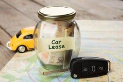 Концепция финансов автомобиля - стекло денег с арендой автомобиля слова, ключом автомобиля Стоковая Фотография RF