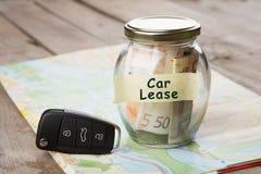 Концепция финансов автомобиля - стекло денег с арендой автомобиля слова, ключом автомобиля Стоковые Фотографии RF