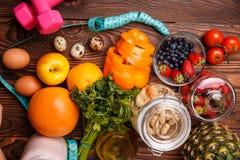 Концепция фитнеса здоровой еды с розовыми гантелями, свежими ягодами, грейпфрутами, яблоками, клубниками и яичками Стоковое Изображение
