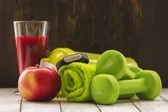 Концепция фитнеса или диеты: гантели, свежий красный smoothie, яблоко Стоковые Изображения