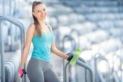 Концепция фитнеса - сексуальная питьевая вода женщины во время разминки и тренировки Разминка на лестницах, сидения на корточках  Стоковые Изображения