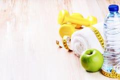 Концепция фитнеса с гантелями, зеленым яблоком и бутылкой с водой Стоковое Изображение RF