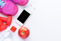 Концепция фитнеса с мобильным телефоном, полотенце, ботинки, гантели, красное яблоко и женщина резвятся обувь над белой предпосыл Стоковое фото RF
