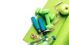 Концепция фитнеса - циновка йоги, яблоко, гантели и прыгая веревочка Стоковое фото RF