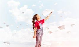Концепция халатного счастливого детства с самолетом бумаги девушки бросая Стоковые Фото