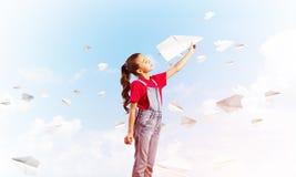 Концепция халатного счастливого детства с самолетом бумаги девушки бросая Стоковые Изображения
