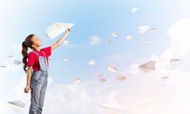 Концепция халатного счастливого детства с самолетом бумаги девушки бросая Стоковые Изображения RF