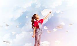Концепция халатного счастливого детства с самолетом бумаги девушки бросая Стоковое Фото