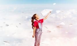 Концепция халатного счастливого детства с самолетом бумаги девушки бросая Стоковое Изображение RF