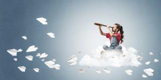 Концепция халатного счастливого детства при девушка смотря в spyglas Стоковые Фотографии RF