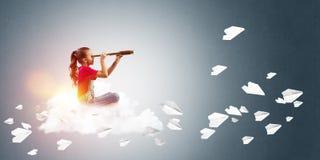 Концепция халатного счастливого детства при девушка смотря в spyglass Стоковые Изображения