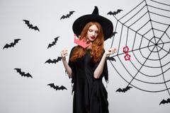 Концепция хеллоуина - красивые девушки в черной ведьме одевают держать упорки партии стоковые фото