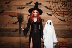 Концепция хеллоуина - мать ведьмы и маленький белый призрак делая фокус или обслуживание празднуя хеллоуин представляя с изогнуты стоковое фото rf