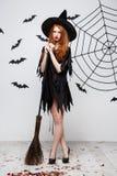 Концепция хеллоуина - счастливая элегантная ведьма наслаждается сыграть с партией хеллоуина broomstick над серой предпосылкой Стоковые Фото