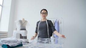Концепция хобби и мелкого бизнеса Молодая женская белошвейка конструирует и шьет одежды сток-видео
