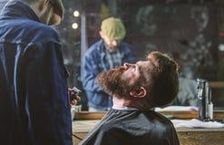 Концепция холить Битник при борода предусматриванная с утеской накидки профессиональным парикмахером в стильной парикмахерскае ba стоковое изображение
