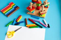 Концепция художнической работы ребенка Альбом для рисовать и покрашенные карандаши на голубой предпосылке Игрушки для Стоковые Фото