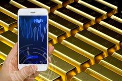 Концепция цены на золото торгуя используя Smartphone или умный прибор к m стоковая фотография rf