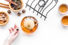 Концепция церемонии чая Рука принимает бак чая около чашек и сухих листьев чая на белом copyspace взгляд сверху предпосылки Стоковое Изображение RF