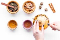 Концепция церемонии чая Рука принимает бак чая около чашек и сухих листьев чая на белом взгляд сверху предпосылки Стоковое Изображение