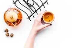 Концепция церемонии чая Рука принимает чашку около бака чая на белом copyspace взгляд сверху предпосылки Стоковые Изображения