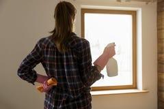 Концепция чистки весны Женщина стоя перед окном с чисткой ткани и окна распыляет готовое для того чтобы помыть окно стоковое изображение