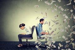 Концепция экономики компенсации работника Женщина работая на компьтер-книжке сидя рядом с человеком под дождем денег Стоковое Фото