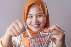 Концепция электронной коммерции, мусульманская дама Holding Мини Вагонетка и кредитная карточка стоковые фото