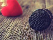 Концепция любителя музыки Черный микрофон на деревянной плите с re Стоковое Фото