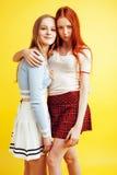 Концепция людей образа жизни: 2 довольно молодых девочка-подростка школы имея усмехаться потехи счастливый на желтой предпосылке Стоковые Фото