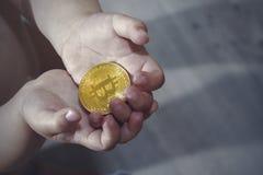 Концепция Bitcoin Bitcoin доли детей Рука и bitcoin ребенка стоковая фотография rf