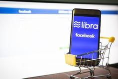 Концепция blockchain монетки Libra со смартфоном на корзине/новом libra проекта cryptocurrency запущенное Facebook смотрит к стоковое изображение rf