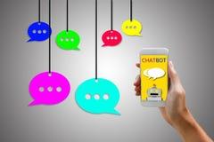 Концепция Chatbot Человек держа smartphone и используя беседовать