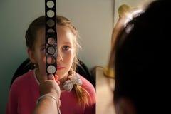 Концепция Optometry - врач с маленькой девочкой увеличителя рассматривая стоковые фото