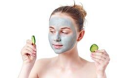 Концепция skincare подростка Девушка подростка при маска сухой глины лицевая держа 2 куска огурца Стоковые Изображения