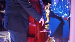 Концерт джаза в концертном зале Человек играя виолончель видеоматериал