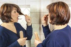 Концы женщины щетки волос удивленные зеркалом разделенные стоковая фотография