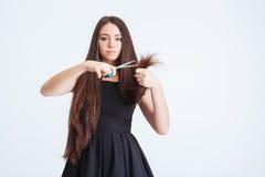Концы серьезного вырезывания женщины разделяя ее длинных хрупких волос Стоковое Фото